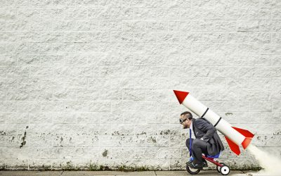 Businessman/entrepreneur in a suit and goggles getting help from the rocket strapped to his back while he is riding a tricycle.